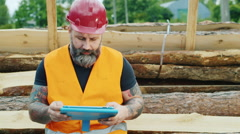 Brutal builder or worker uses a tablet in a break from work - stock footage