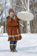 Woman in Koryak national dress dancing, beats the tambourine and singing - stock photo