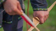 Putting an arrow on a bow - stock footage