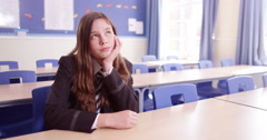 4K Bored young girl sitting on her own & daydreaming in school classroom.  Stock Footage