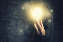 Hooded unidentifiable person holding light bulb - stock photo
