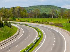 Two-lane highway turned to the left Stock Photos