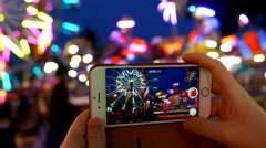 Recording people playing carnival rides on iphone - stock footage