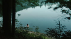 Beautiful naked brunette siren girl swimming in the foggy mystical mountain lake - stock footage