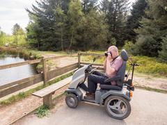 Senior enjoying the main Tarn Area with the help of a Tramper Mobility Scoote - stock photo