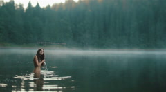 Beautiful naked fairy or mermaid with long dark hair touches the surface of Stock Footage