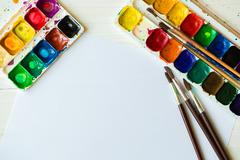 Watercolors and paint brush on white wooden background - stock photo