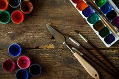 Watercolors and paint brush on wooden background - stock photo