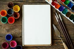 Paper, watercolors and paint brush on wooden background Stock Photos
