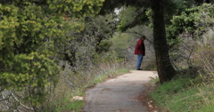 Man walks forward mountain forest trail in spring DCI 4K Stock Footage