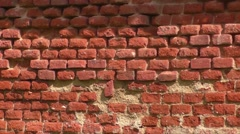 Background of old vintage crumbling brick wall on bright sunny day - stock footage