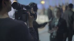 The cameraman shoots the interview (seen from behind) Stock Footage