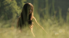 Close up of beautiful young naked girl nymph with long dark hair in the green Stock Footage