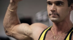 Man with an intense expression on his face training in the gym his biceps and Stock Footage
