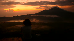 Girl watching sunrise over Lake Batur, Volcano Agung and Abang, Bali, Indonesia Stock Footage