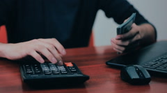 A man with calculator and bills counting money. Finances, business, economy - stock footage