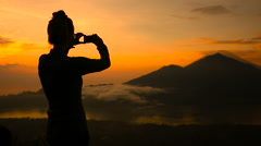 Girl taking pictures of sunrise over Lake Batur, Volcano Agung and Abang, Bali Stock Footage