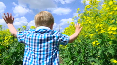 Happy child running in flowers - stock footage