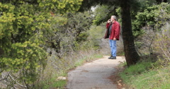 Man walks mountain forest trail talking on cell phone DCI 4K - stock footage