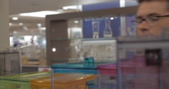 Man looking at plastic containers in the shop Stock Footage
