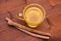 Cup of herbal tea licorice in wooden table top view - stock photo