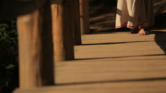 Close up of barefoot woman in long embroidered traditional dress walking on the Stock Footage