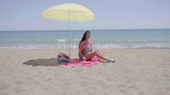 Lone woman sitting on beach under umbrella Stock Footage