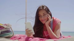 Ground level view of woman using phone at beach Stock Footage