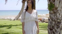 Smiling woman walking near palm trees Stock Footage
