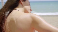 Young woman applying sunscreen to a shoulder Stock Footage