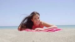 Excited attractive young woman lying on a beach Stock Footage