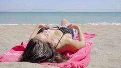 Young woman sunbathing on a tropical beach Stock Footage