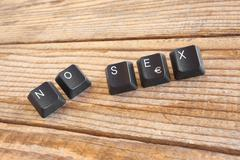 """NO SEX"" wrote with keyboard keys on wooden background - stock photo"