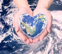 World in heart shape with over women human hands on blurred natural backgroun Stock Illustration