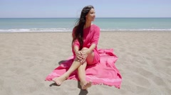 Pretty young woman sunbathing in a pink tunic Stock Footage