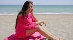 Sexy young woman sitting on a beach - stock footage