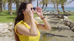 Smiling vivacious young woman in sunglasses - stock footage