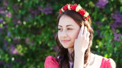 Woman in a red dress with a wreath in spring garden Stock Footage