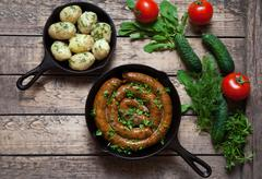 Meat sausage roasted in cast iron skillet with boiled potatoes - stock photo