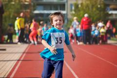 Young preschool children, running on track in a marathon competition - stock photo