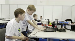 Children work on a computer to create a robot Stock Footage