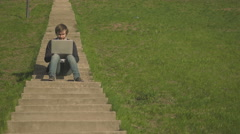 Front View of Young Man Sitting On The Stairs In Park Using Laptop Stock Footage