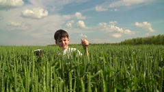 Boy Starts Up the Paper Plane in the Field of Wheat Against the Blue Summer Sky Stock Footage