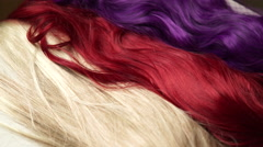 4K Blonde, Red, Purple wigs placed on rustic painted white table Stock Footage