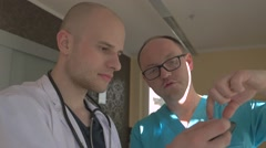 Two doctors are looking at their patient x-ray on the mobile phone. Stock Footage