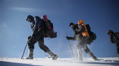 Hikers go through the snow in the mountains Stock Footage