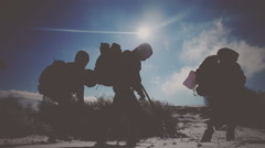 Hikers go through the snow in the mountains under the rays of the winter sun Stock Footage
