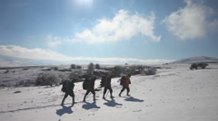 Hikers go through the snow in the mountains in winter Stock Footage
