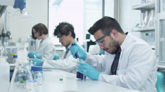 Team of Multiethnic Students in Coats Working in Laboratory Stock Footage