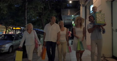 Family carrying shopping bags in the street with stores Stock Footage